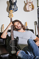 Portrait of man sitting on couch holding a guitar
