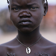 Sudan. Agiep. Famine. Young girl with ritual scarring on her chest and cowrie shell necklace