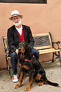 A man wearing a hat sits with his dog along East Bay Street in historic Charleston, SC.