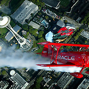 "The Oracle Challenger, a unique 400 horespower stunt plane, makes a pass over a familiar Seattle landmark while on an aireal tour of the area on Thursday August 5, 2004 in preparation for  the KeyBank Airshow at SEAFAIR.  Sean Tucker, pilot of the plane, was recently named by the Smithsonian Air and Space Museum as one of the twenty-five ""Living Legends of Flight.""   The highly regarded pilot has won numerous awards for airshow showmanship and aerobatics at competitions and airshows across the nation.  Joshua Trujillo / Seattle Post-Intelligencer"
