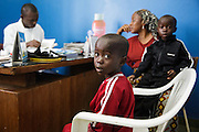 Katy Cherif, 40, and her twin sons Lacine (left) and Lusseini, both 4 and suffering from malaria and diarrhea, meet with a nurse at the Libreville health center in Man, Cote d'Ivoire on Wednesday July 24, 2013.