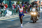 Mo Farah passes through Canary Wharf about thirty seconds behind the leaders. The London Marathon starts in Greenwich on Blackheath passes through Canary Wharf and finishes in the Mall. London UK, 13 April 2014.  Guy Bell, 07771 786236 guy@gbphotos.com