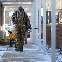 Jason Bridges, a Tupelo Public School District Maintenance Department employee, uses a shovel to spread salt on the sidewalks inside the walkways at Lawhon Elementary School on Wednesday morning. All the Tupelo Public School District schools were treated for icy walkways in preparation for the possibility of students returning to school on Thursday.