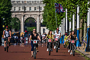 A man with a thank you NHS union jack flag follows a group of santander hire bikes - Enjoying cycling on The Mall as the sun comes out again. The 'lockdown' continues for the Coronavirus (Covid 19) outbreak in London.