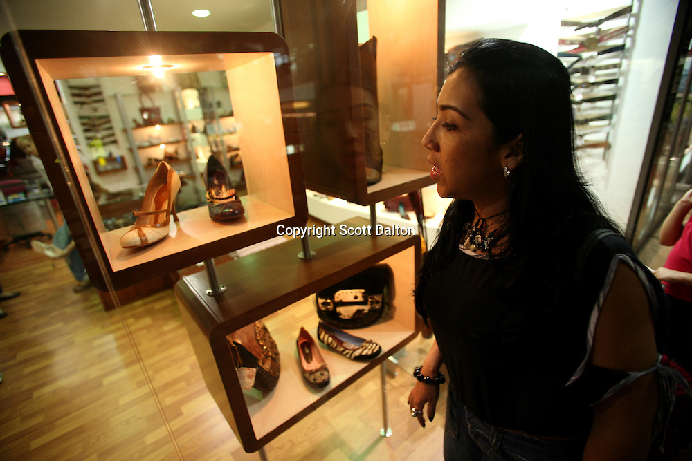 A woman looks at shoes at a shopping mall in an exclusive area of Medellin on Saturday, April 28, 2007. (Photo/Scott Dalton)