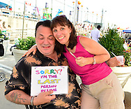 "Brooklyn, New York, USA. 10th August 2013. LARRY MCGOWAN is holding a sign ""Sorry, I'm the last person on line"" that volunteer artist LAURA YORBURG uses when painting designs on visitors during the 3rd Annual Coney Island History Day celebration."