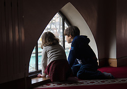 Finsbury Park Mosque, London, February 7th 2016. Two children peer out of the upper floor window of Finsbury Park Mosque as part of a Visit My Mosque initiative by the Muslim Council of Britain to show non-Muslims &ldquo;how Muslims connect to God, connect to communities and to neighbours around them&rdquo;.<br /> . ///FOR LICENCING CONTACT: paul@pauldaveycreative.co.uk TEL:+44 (0) 7966 016 296 or +44 (0) 20 8969 6875. &copy;2015 Paul R Davey. All rights reserved.