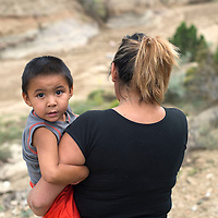 Lisa R. Benally carries her son Elijah John Benally to the spot her 2013 Chevy Impala landed at the base of an arroyo off Zuni Drive In road Wednesday.