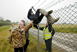 © Licensed to London News Pictures. 08/10/2012. Hinkley Point, Somerset, UK. Picture of protesters trying to scale the perimeter fence, as anti-nuclear campaigners hold a mass trespass protest at the site of Hinkley Point nuclear power station.  Energy company EDF plans to build a new nuclear power plant at the site called Hinkley C.  08 October 2012..Photo credit : Simon Chapman/LNP.