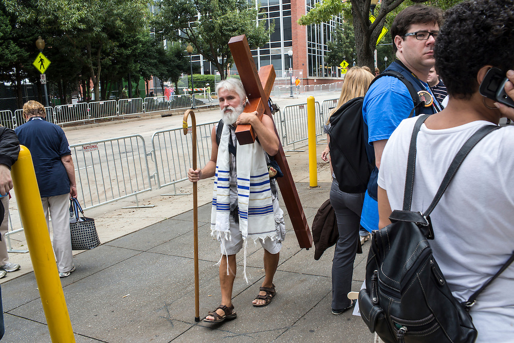 A man carries a cross through the streets among delegates and media ahead of the Democratic National Convention on Tuesday, September 4, 2012 in Charlotte, NC.