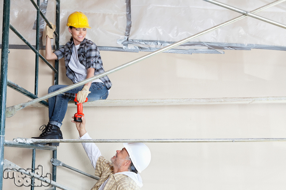 Male architect giving drill to female worker on scaffold at construction site