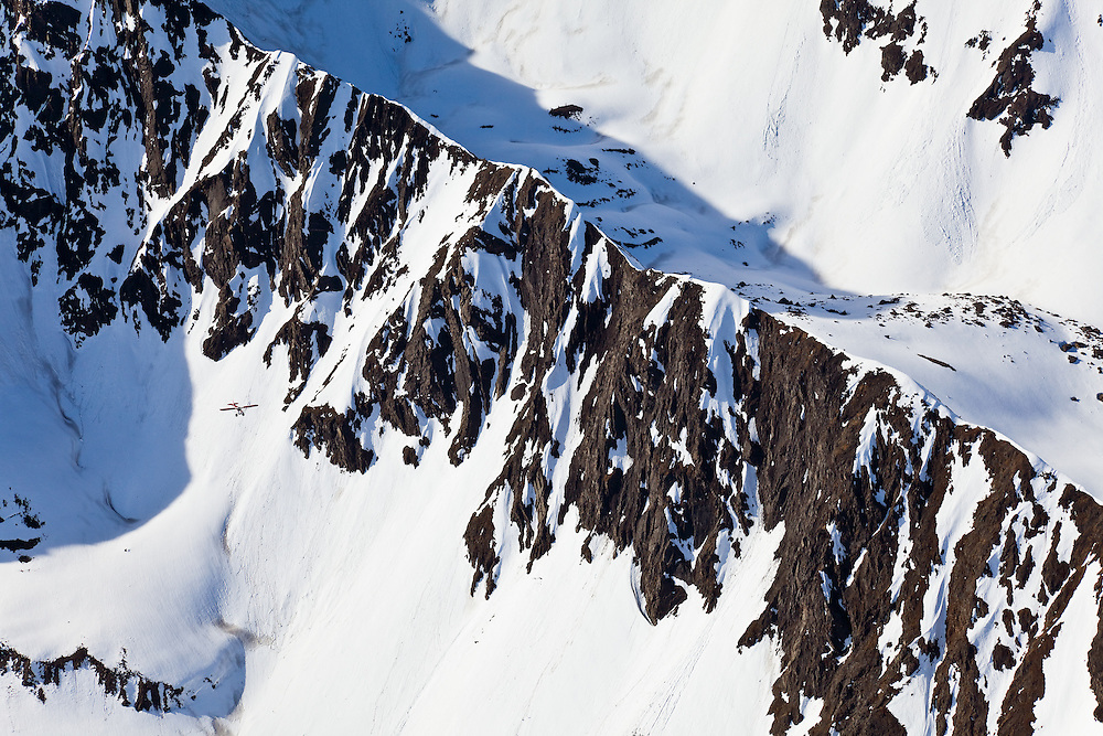 Aerial of an airplane flying along the snow covered ridgeline of the Chugach Mountains in Chugach State Park near Anchorage in spring in Southcentral Alaska. Morning.