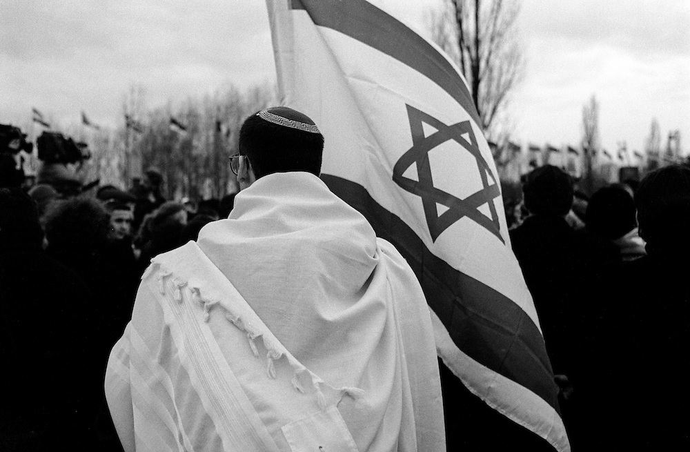 A visitor at the Auschwitz (Birkenau) Nazi concentration camp is holding a jewish flag during the ceremony to remember the 50th anniversary of the liberation in 1995. It is estimated that between 1.1 and 1.5 million Jews, Poles, Roma and others were killed here in the Holocaust between 1940-1945.
