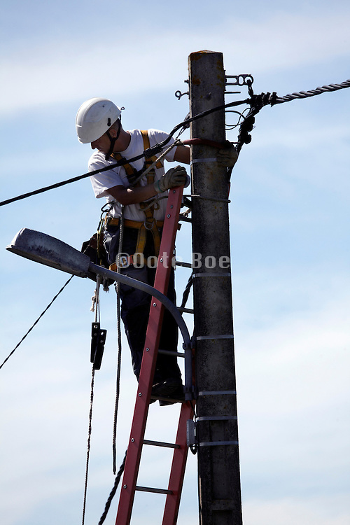utility worker high up balancing on a ladder