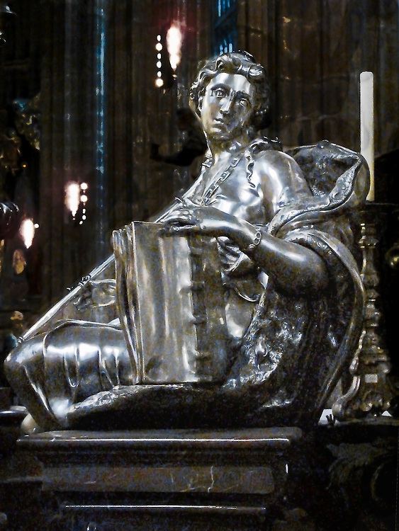 Silver and silver-gilt sculpture on the tomb of tomb of St John of Nepomuk in the Cathedral of St Vitus, Prague.  a Baroque monument cast in silver and silver-gilt that was designed by Fischer von Erlach, 1736.  Detail of a seated female figure holding a large book upright with her left hand and looking mournfully over her shoulder.