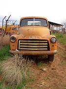 An old rusty truck abandoned beside a field.