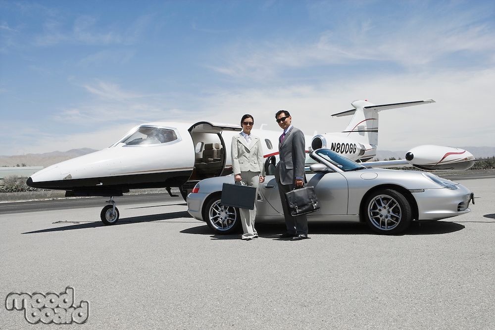Mid-adult businesswoman and mid-adult businessman standing in front of convertible and private jet on landing strip.