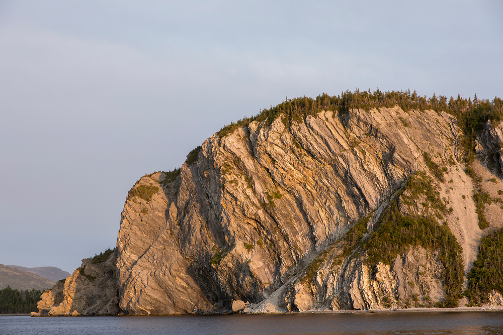 Canada, Newfoundland, Bonne Bay, Setting sun lights cliffs along East Arm in Gros Morne National Park on summer afternoon