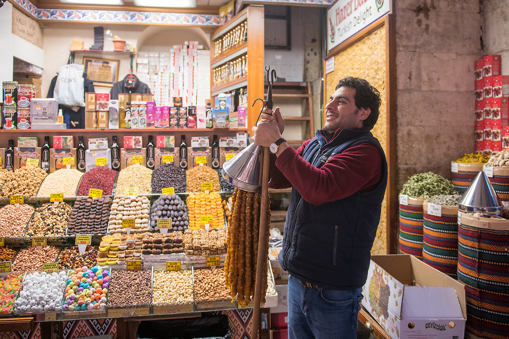 Adult male prepares hanging mechanism full of sweets in front of shop in Istanbul Spice bazaar in Turkey