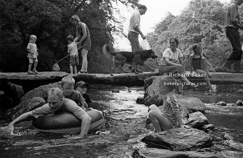 On a busy Summer weekend, families enjoy the old Tarr Steps Clapper Bridge over the River Barle in Exmoor National Park, Devon, England. Crossing on the huge stone prehistoric slabs which weigh up to 5 tons apiece, children play with fishing nets, walk dogs and sit enjoying the view below of others who mess about in a small inflatable dinghy on the flowing stream. Located in a National Nature Reserve about 2.5 miles (4 km) south east of Withypool and 4 miles (6 km) north west of Dulverton, this spot is a favourite tourist place in South-West England. This typical clapper bridge construction may date to around 1000 BC. It is 180 feet (55 m) long and has 17 spans and designated by English Heritage as a grade I listed building.