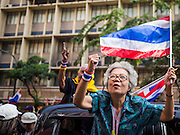 """20 DECEMBER 2013 - BANGKOK, THAILAND:  An anti-government protestor leans out of her car window on Silom Road to chant """"Yingluck Get Out!!"""" during a protest in Bangkok. Thousands of anti-government protestors, supporters of the so called Peoples Democratic Reform Committee (PRDC), jammed the Silom area, the """"Wall Street"""" of Bangkok, Friday as a part of the ongoing protests against the caretaker government of Yingluck Shinawatra. Yingluck dissolved the Thai Parliament earlier this month and called for national elections on Feb. 2, 2014. The protestors want the elections postponed and the caretaker government to step down. The Thai election commission ruled Friday that the election would go on dispite the protests.         PHOTO BY JACK KURTZ"""