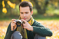 Young man photographing in park during autumn