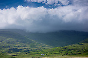 Solitary white croft farmhouse and farm barn nestling below mountain range by loch under moody sky and rolling clouds on Isle of Mull in the Inner Hebrides and Western Isles of Scotland