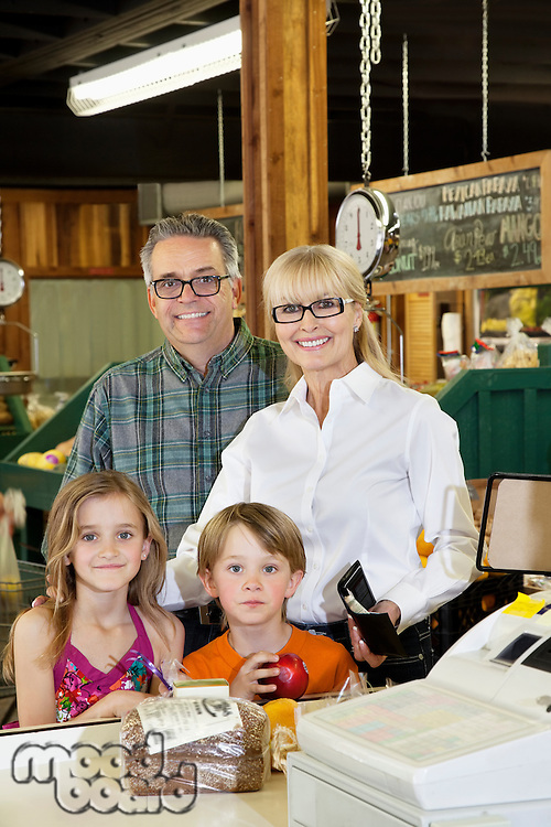 Portrait of a happy grandparents with children standing at checkout counter in market