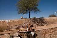 A boy collects water from his village's only water source, on October 13, 2011, in Manzoorabad, Pakistan. The water comes from a local contaminated river. According to UN reports, hundreds of thousands of children in Pakistan suffer from severe-acute-malnutrition, with 15.1% of children experiencing acute malnutrition. Child malnutrition has breached emergency levels in Pakistan's Sindh province, after monsoon floods devastated the country's poorest region for a second year. Extreme poverty, poor diet and health, exposure to disease, and inadequate sanitation and hygiene annually produce alarming levels of malnutrition amongst children, but the floods have increasingly endangered an already vulnerable population. (Photo by Warrick Page)