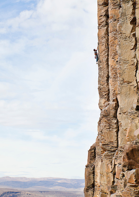 A man climbing a basalt rock cliff in central Washington State, USA.