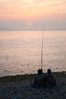 New York, Long Island - 2 people sitting on the shore, fishing at sunset.