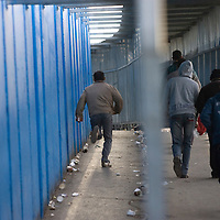 Late Palestinian workers rush inside the checkpoint 300, the crossing passage between Bethleem and Jerusalem, on December 15. 2010 in Bethleem. Workers arrived every day at two o'clock in the morning  to catch a place at the entrance of the checkpoint, so they can arrived at time to their work in the Israeli side. Photo by Olivier Fitoussi
