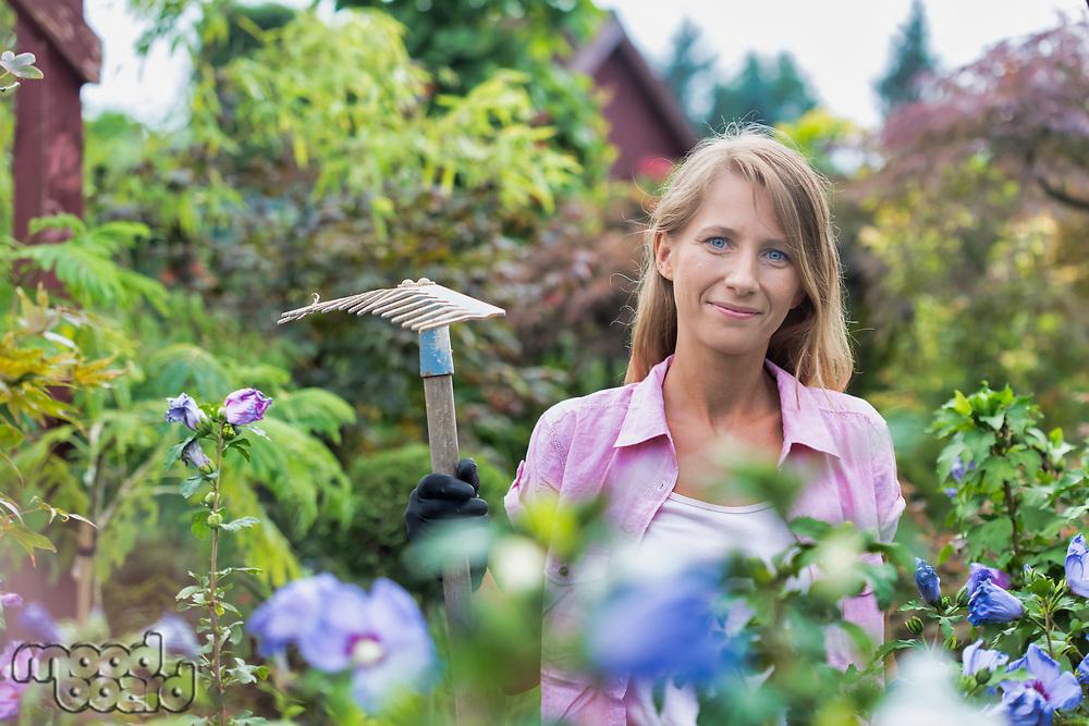 Portrait of beautiful gardener holding fork rake