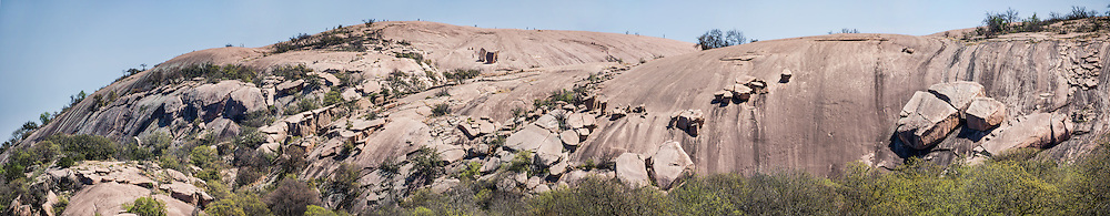 """Explore a large pink granite dome at Enchanted Rock State Natural Area, between Fredericksburg and Llano, Texas, USA. Enchanted Rock is a fascinating exfoliation dome (with layers like an onion), rising 425 feet (130 m) above its surroundings to elevation of 1825 feet (556 m) above sea level, in the Llano Uplift. Geologically, the exposed rock (monadnock or inselberg, """"island mountain"""") is part of a pluton (bubble of rock slowly crystallized from magma) within the billion-year-old igneous batholith, Town Mountain Granite (covering 62 square miles mostly underground), which intruded from a deep pool of hot magma 7 miles upwards into the older metamorphic Packsaddle Schist. The overlying sedimentary rock (Cretaceous Edwards limestone) eroded away to expose the prominent domes seen today: Enchanted Rock, Little Rock, Turkey Peak, Freshman Mountain, and Buzzard's Roost. This panorama was stitched from 6 overlapping photos."""