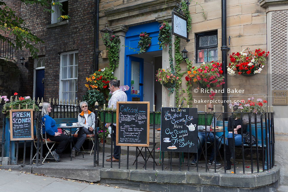 Customers chat with cafe owner outside on an historical street, on 24th September, 2017, in Durham, England.