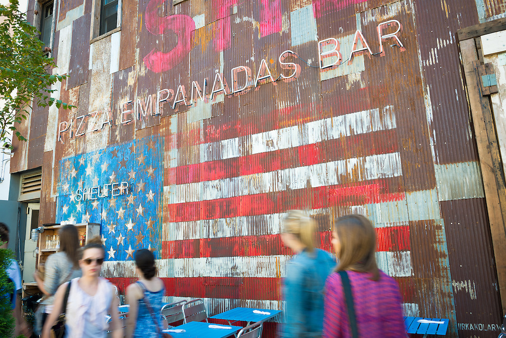People passing by a cafe in Williamsburg, Brooklyn with American flag painted on wall.