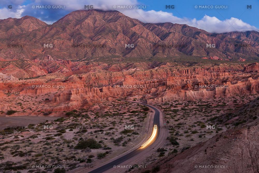AUTO PASANDO EN LA RUTA 68 ENTRE LA QUEBRADA DE LAS CONCHAS AL ANOCHECER, CAFAYATE, PROVINCIA DE SALTA, ARGENTINA (PHOTO © MARCO GUOLI - ALL RIGHTS RESERVED)