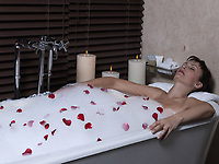 beautiful calm and serene woman in palace hotel room in a bathtub with rose petals and foam