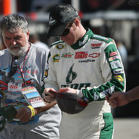 Sprint Cup Series driver Dale Earnhardt Jr. (88) signs autographs at the Daytona International Speedway on February 18, 2011 in Daytona Beach, Florida. (AP Photo/Alex Menendez)