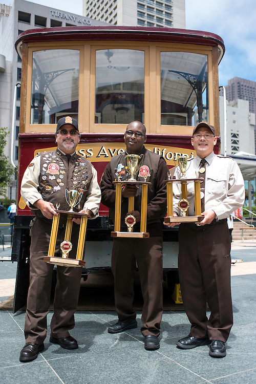 (l to r) 2nd place professional division bell ringer Ken Lunardi, 2013 Bell Ringing Champion Trini Whittaker, 3rd place professional bell ringer Joseph Sue pose in front of Cable Car 62 at the 50th Cable Car Bell Ringing Competition in San Francisco's Union Square | July 11, 2013
