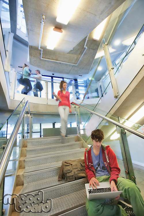 University student using computer on staircase