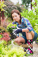 Portrait of female gardener examining plants on pot