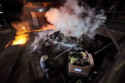 An Arcelor-Mittal employee, sprays water to cool down machinery used to operate blast furnace B, at the Ougree facility near Liege, Belgium, Monday, Feb. 9, 2009. (Photo © Jock Fistick)