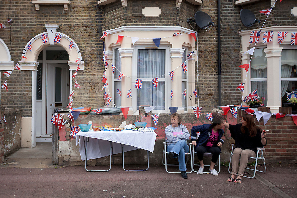 © Licensed to London News Pictures. 02/06/12. LONDON, UK. Residents of Ravenscroft Road in Canning Town, East London, are seen outside their Union Jack adorned homes during a Jubilee street party. The Royal Jubilee celebrations. Great Britain is celebrating the 60th  anniversary of the countries Monarch HRH Queen Elizabeth II accession to the throne this weekend Photo credit : LNP