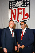 NFL Commissioner Pete Rozelle (left) smiles as he poses for a photo with an unidentified executive under an NFL shield banner during the 1987 NFL Draft on April 28, 1987 in New York, N.Y. (©Paul Anthony Spinelli)