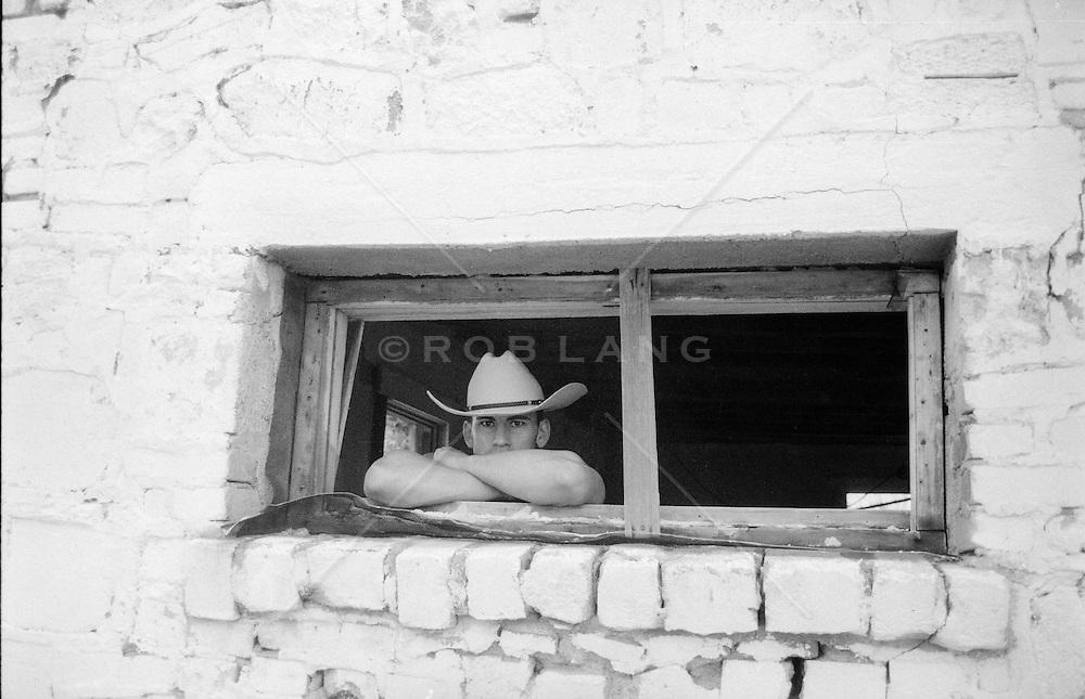 cowboy in a rustic barn window