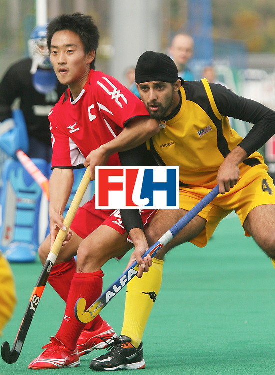 Kakamigahara (Japan):  Ono Tomonori of Japan being shadowed by Baljit Singh of Malaysia in the Olympic Hockey Qualifier at Gifu Perfectural Green Stadium at Kakamigahara on 12 April 2008.  Photo: GNN/ Vino John