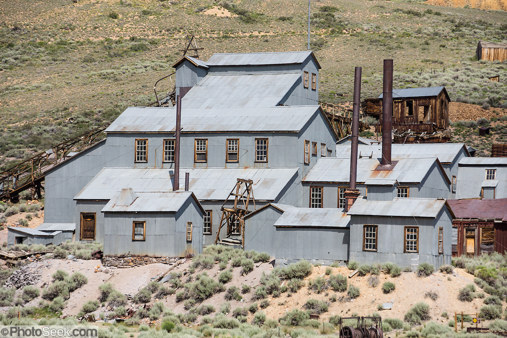 "The gray-metal-sided Standard Stamp Mill is preserved at Bodie, California's official state gold rush ghost town. Bodie State Historic Park lies in the Bodie Hills east of the Sierra Nevada mountain range in Mono County, near Bridgeport, California, USA. After W. S. Bodey's original gold discovery in 1859, profitable gold ore discoveries in 1876 and 1878 transformed ""Bodie"" from an isolated mining camp to a Wild West boomtown. In the 1870s, the Bunker Hill Mine, later renamed the Standard Mining Company, made a rich strike of gold and silver ore yielding nearly $15 million in 25 years. By 1879, Bodie had a population of 5000-7000 people with 2000 buildings. At its peak, 65 saloons lined Main Street, which was a mile long. Bodie declined rapidly 1912-1917 and the last mine closed in 1942. Bodie became a National Historic Landmark in 1961 and Bodie State Historic Park in 1962."