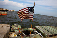 American flag stained with BP oil on Dauphin Island. Sand burms have been built by the National Guard on Dauphin Island in Alabama to protect the islands marshland. BP Oil  washed up on beach on Dauphin Island. As of June 13th 2010,  work crews have been able to keep up with the clean up, though the western part of the island is closed off.