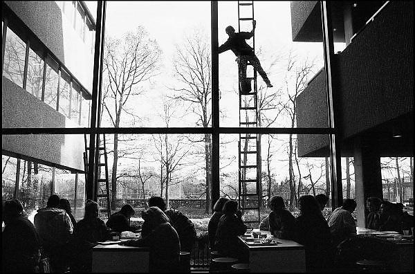Nederland, Nijmegen, 11-4-1990Een glazenwasser lapt de ramen van een. Glazenwasser op een ladder maakt de ramen van een gebouw van de universiteit Nijmegen schoon. Vanwege Europese arbo wetgeving mogen zij niet meer vanaf ladders werken, maar op steigers of hoogwerkers. Foto: Flip Franssen/Hollandse Hoogte